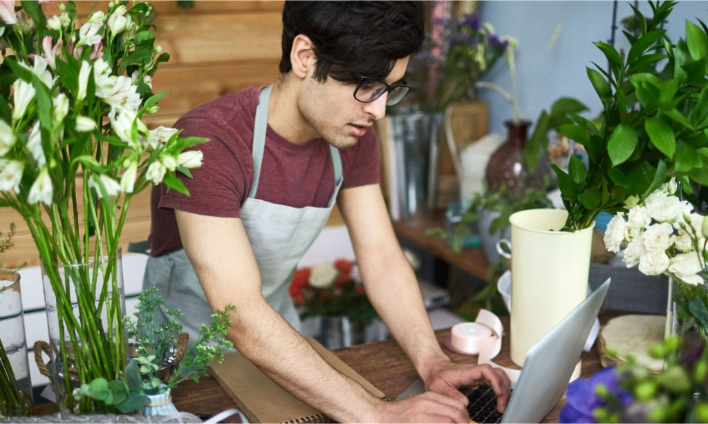 Invoicing: Young man in flower shop types on a laptop.
